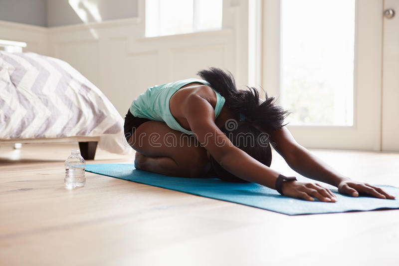 Young black woman practicing yoga in the cat stretch pose stock images