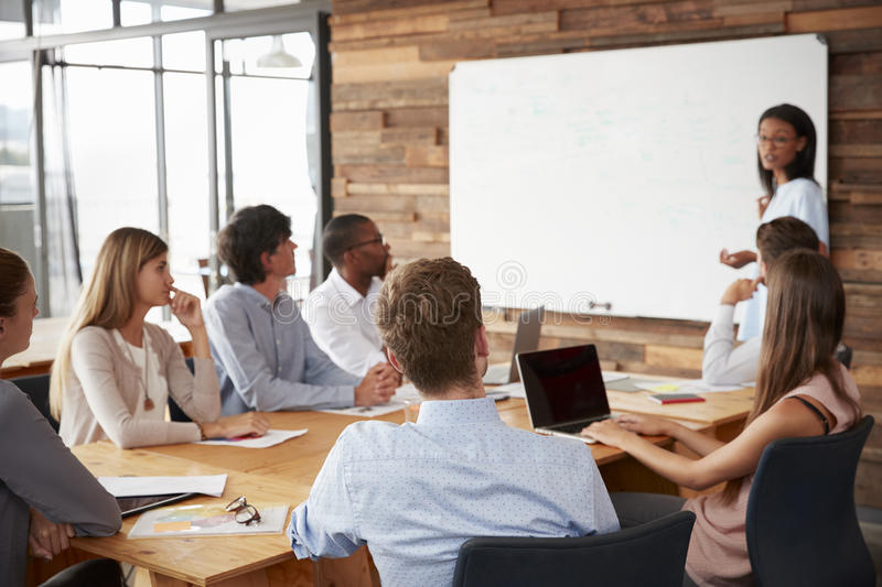 Young black woman presenting to colleagues from whiteboard�. Young black women presenting to colleagues from whiteboard stock images