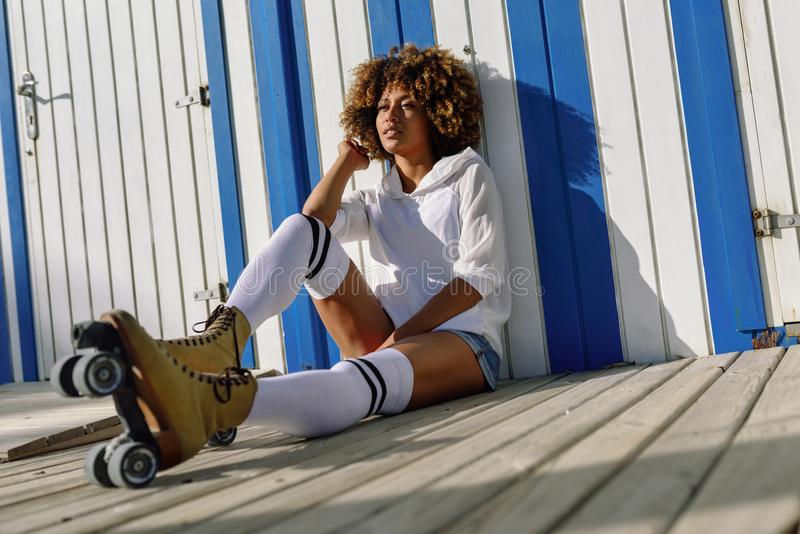 Young black woman on roller skates sitting near a beach hut. stock photography
