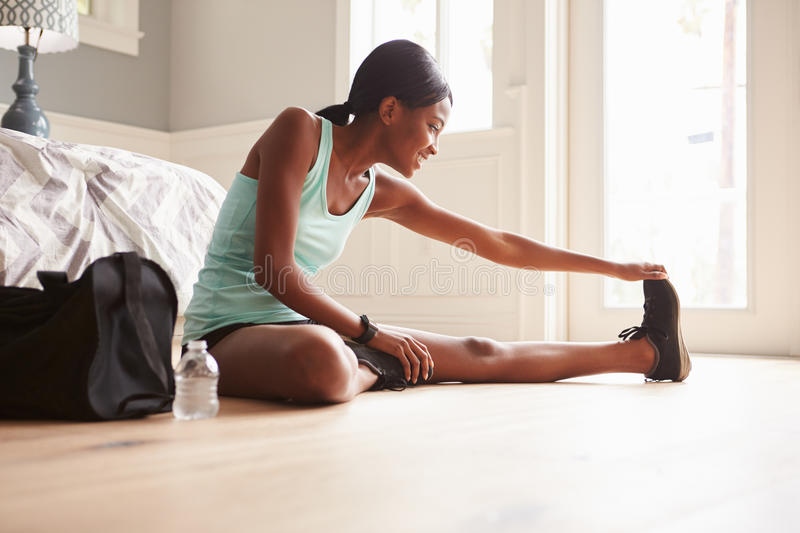Young black woman sitting on the floor at home stretching stock images