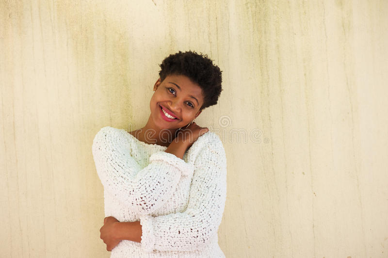 Young black woman smiling with white sweater royalty free stock photography
