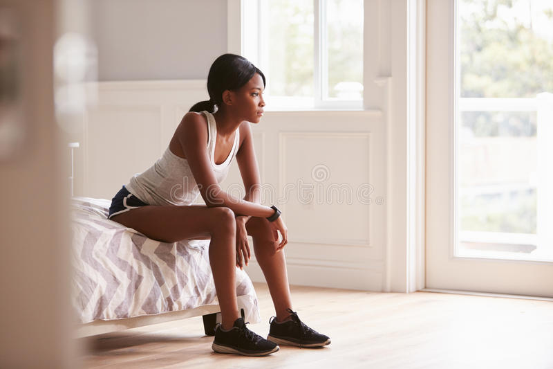 Young black woman in sports clothes sitting on bed at home stock photo