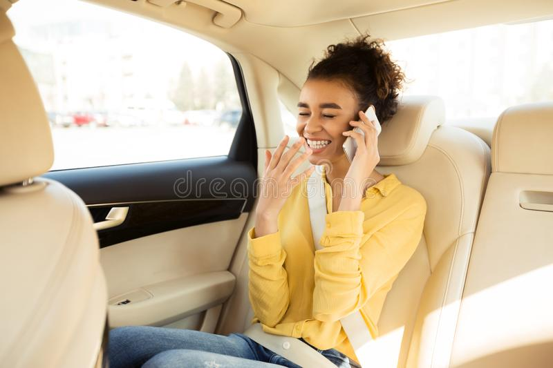 Young black woman talking on phone in car royalty free stock photography