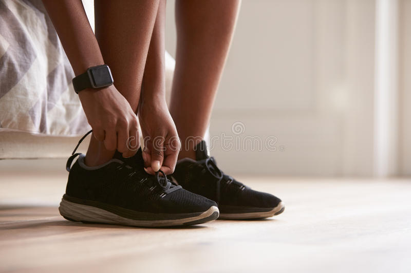 Young black woman tying sports shoes, close-up royalty free stock photos