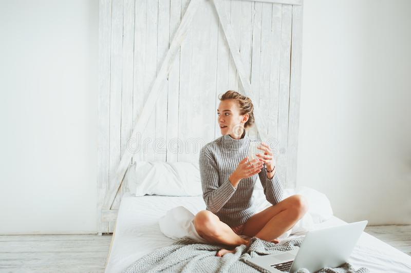 Young blogger or business woman working at home with social media, drinking coffee in early morning in bed. Modern living in scandinavian interior, casual royalty free stock image