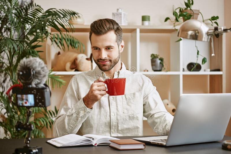 Young blogger. Male young vlogger recording social media video and drinking tea while looking at camera stock images