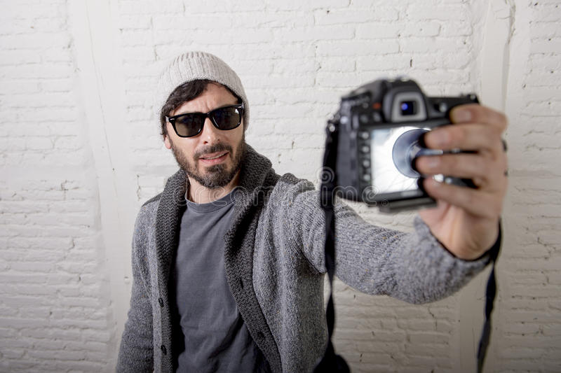Young blogger man hipster style holding photo camera shooting selfie video and photo royalty free stock image
