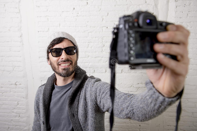 Young blogger man hipster style holding photo camera shooting selfie video and photo stock image