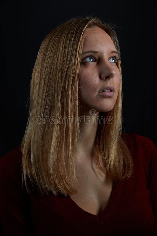 Young blond woman looks up hopefully royalty free stock images