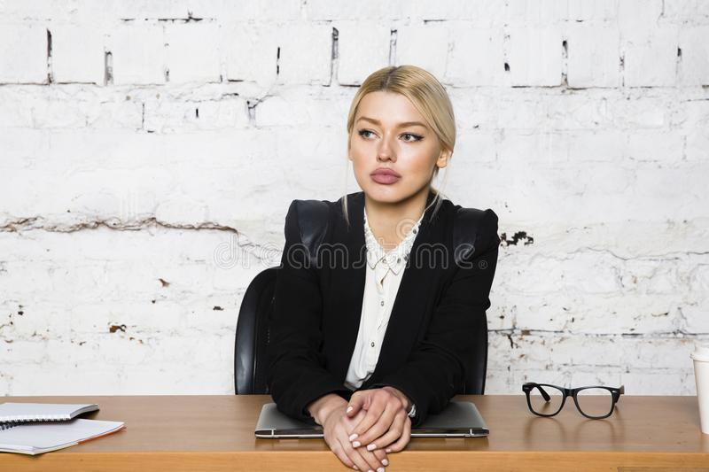 Young blond beauty businesswoman sitting at a office table with laptop, notebook and glasses in suit. Business concept. royalty free stock images