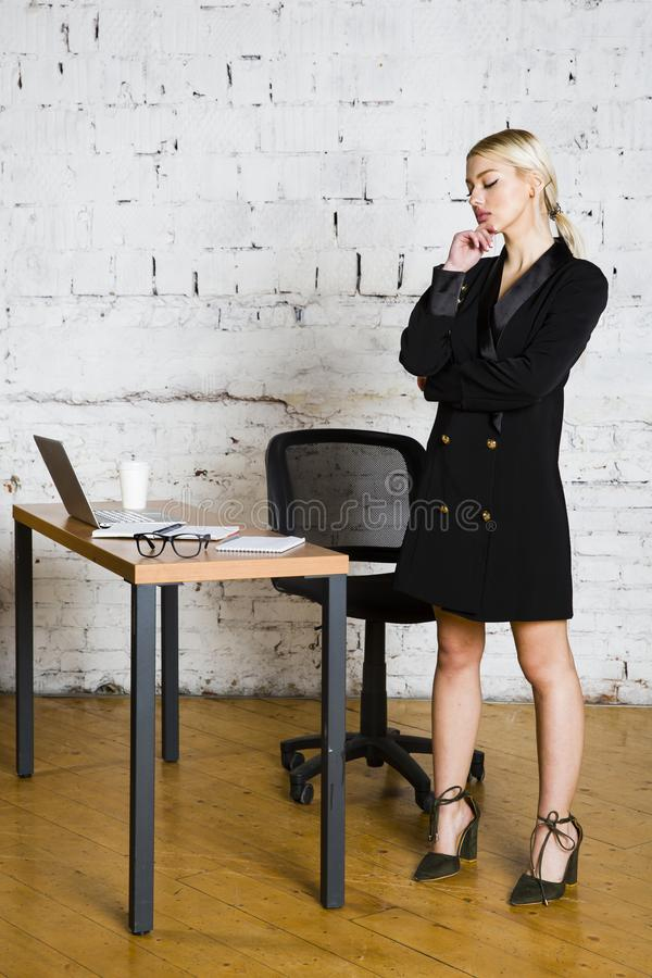 Young blond beauty businesswoman sitting at a office table with laptop, notebook and glasses in suit. Business concept. stock photos