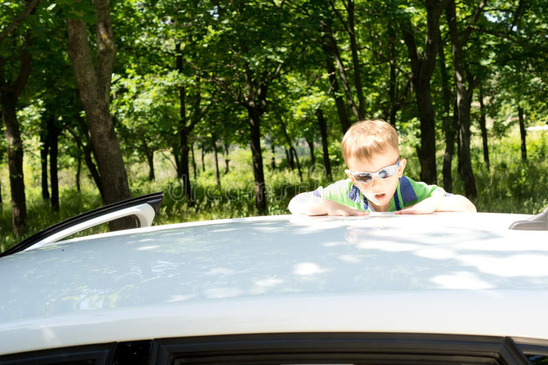 Download Young Blond Boy Climbing To The Rooftop Of A Car Stock Photo - Image of outdoors, playful: 31333834