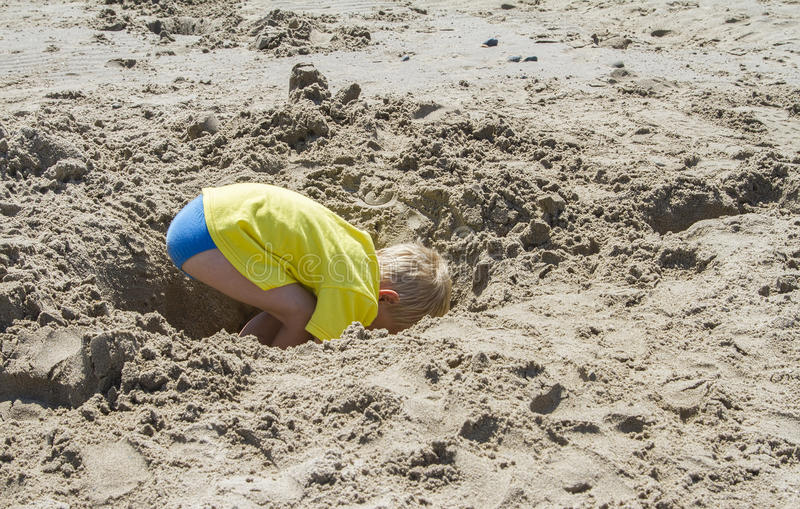 Young blond boy digging a hole royalty free stock image