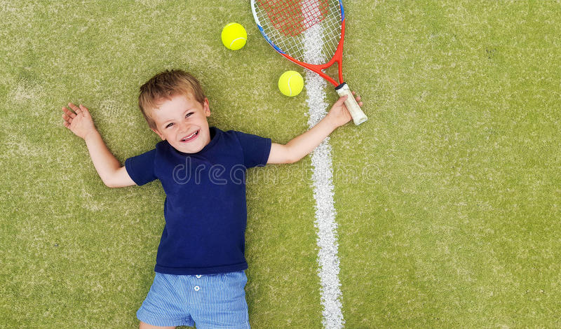 A young blond boy smiling and laying on a tennis court, with racket and balls. stock images