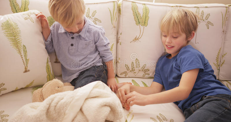 Young blond boy tickling his brother's feet on a sofa.  stock photos