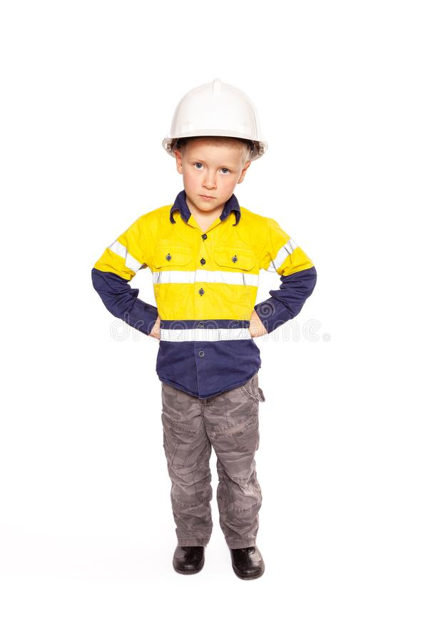 Young blond caucasian boy fists on hips role playing as an angry construction worker in a yellow and blue hi-viz shirt royalty free stock photography