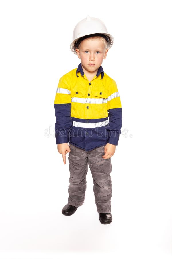 Young blond caucasian boy pointing down with a fierce look role playing as a construction worker supervisor stock image