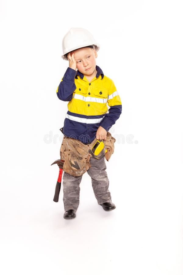 Young blond caucasian boy scratching his head in disbelief role playing as a frustrated construction worker stock photography