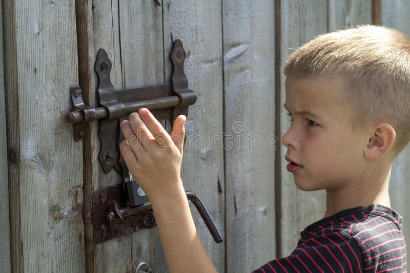 Young blond cute boy trying to open rusty slide bolt lock on lit by sun closed old wooden barn door. Children curiosity, love for. Adventures, safety, security stock photography