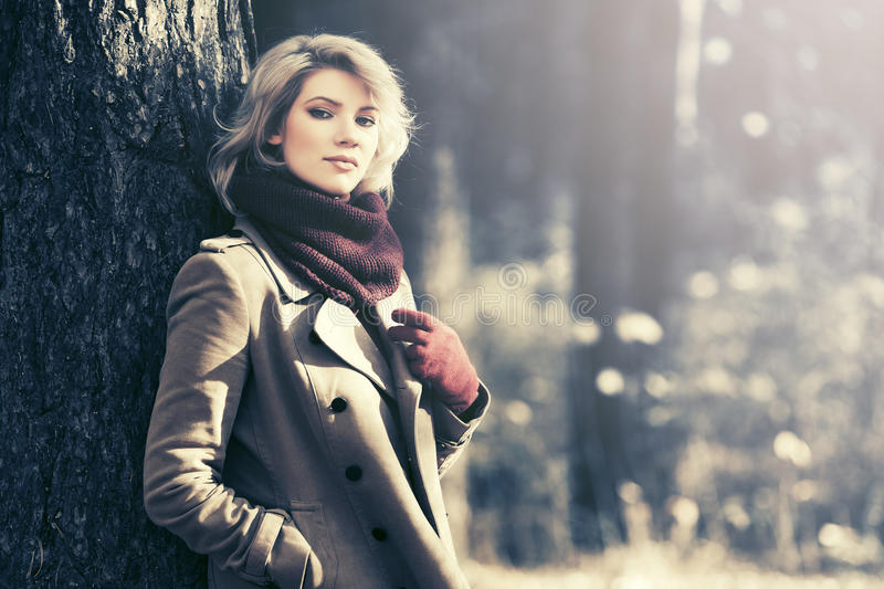Young blond fashion woman in autumn forest royalty free stock photography