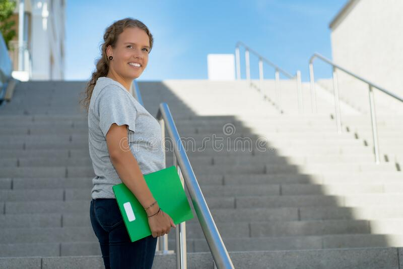 Young blond female student walking to university stock images