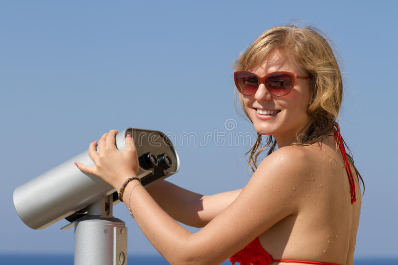Young blond girl with binoculars. Happy blond girl with binocular for tourists does sightseeing royalty free stock photography