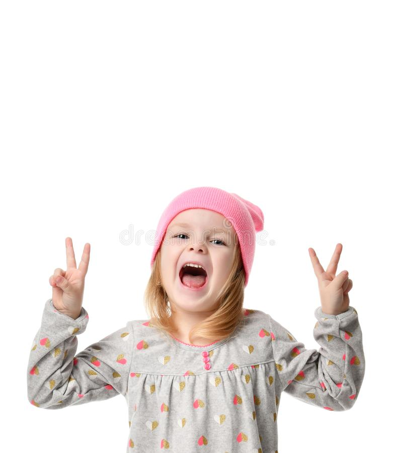 Young blond girl in birthday party princess hat hands show peace sign screaming. Isolated on a white background royalty free stock images