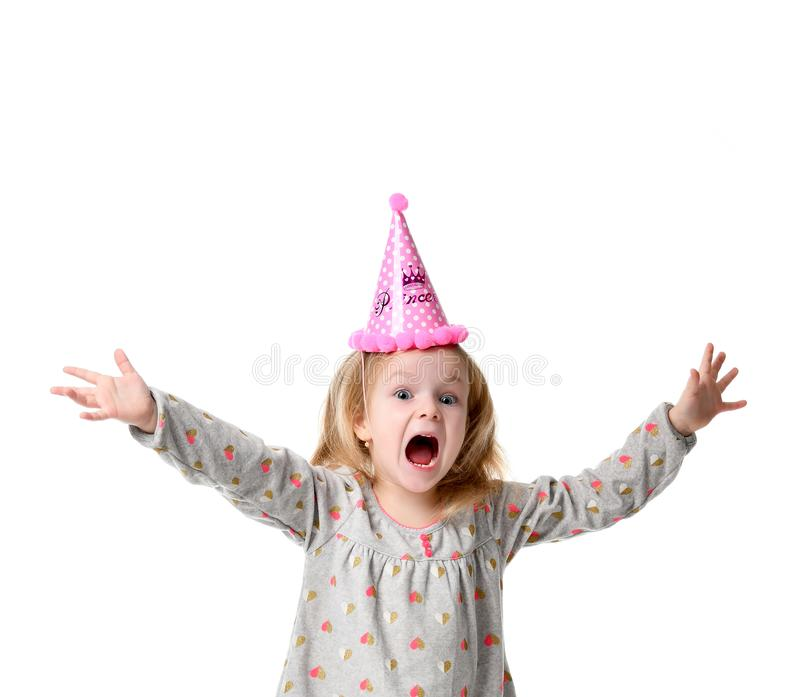 Young blond girl in birthday party princess hat hands spread up screaming. Isolated on a white background royalty free stock photography