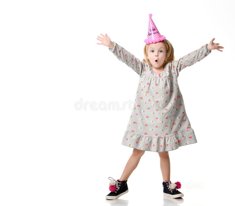 Young blond girl in birthday party princess hat hands spread up screaming stock photos
