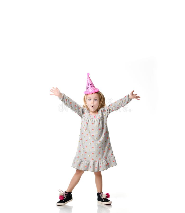 Young blond girl in birthday party princess hat surprised emotions with hands spread up isolated on a white. Background royalty free stock photo