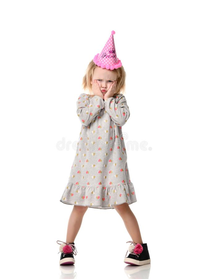 Young blond girl in birthday party princess hat upset sad emotions royalty free stock photos
