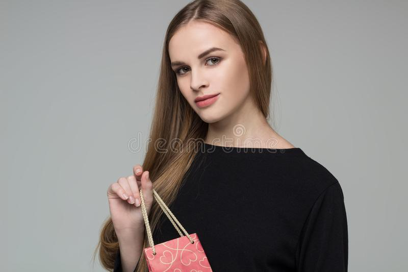 Young blond girl in black holds red gift present package royalty free stock image