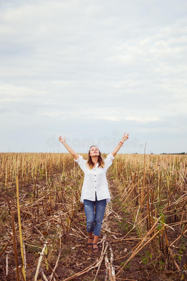 Young blond girl in casual clothes with arms raised enjoys her walking in field. royalty free stock photography