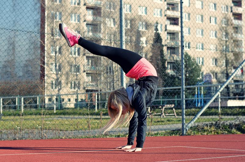 Young blond girl dancing break dance. On the street stock photos