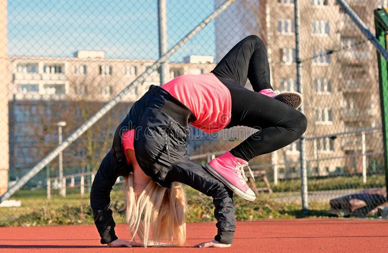 Young blond girl dancing break dance. On the street royalty free stock image