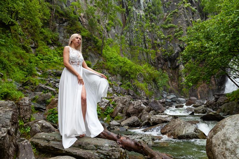 A young blond girl in an elegant pose bares her leg while reclining the hem of a boudoir dress, in the mountains against waterfall. And stones, like a ballerina royalty free stock photography