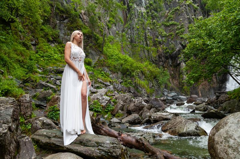 A young blond girl in an elegant pose bares her leg while reclining the hem of a boudoir dress, in the mountains against waterfall. And stones, like a ballerina stock images