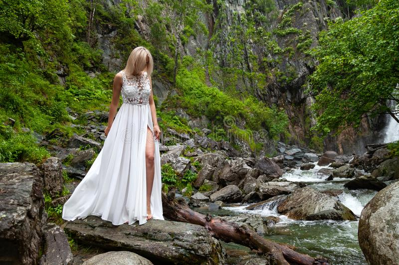 A young blond girl in an elegant pose bares her leg while reclining the hem of a boudoir dress, in the mountains against waterfall. And stones, like a ballerina royalty free stock images