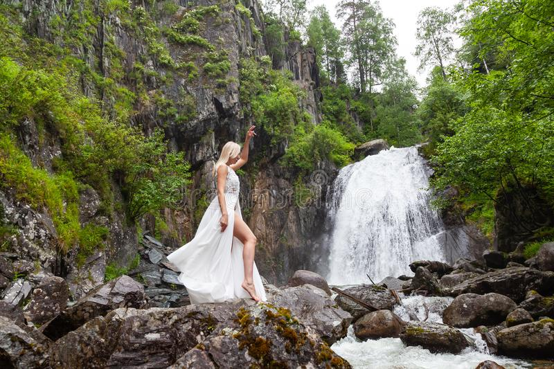 A young blond girl in an elegant pose bares her leg while reclining the hem of a boudoir dress, in the mountains against waterfall. And stones, like a ballerina stock photography