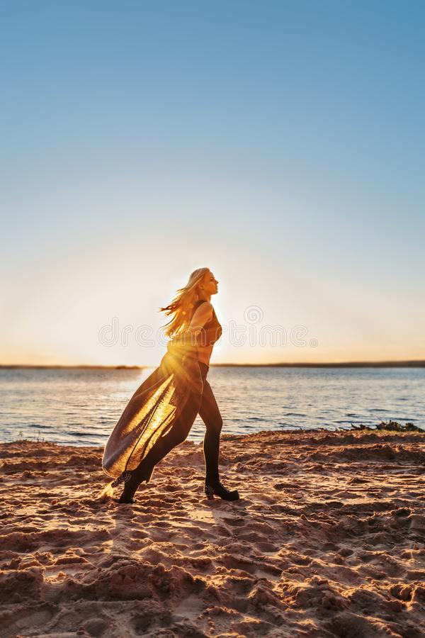Young blond girl with fluttering hair and clothes running along the beach in bright highlights glare and rays of the rising sun. Young blond woman with royalty free stock photography