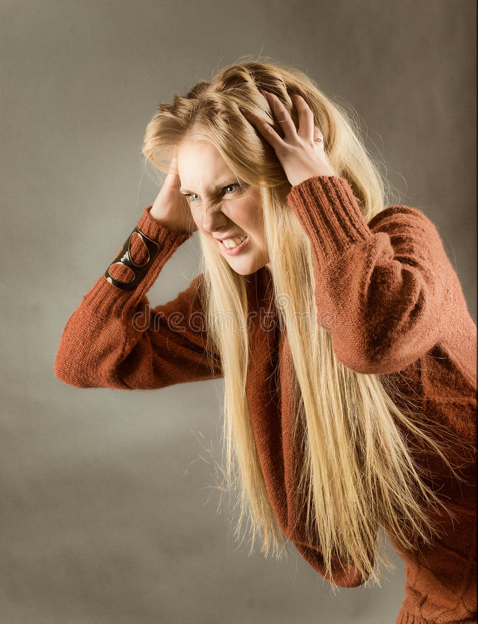 Young blond girl furiously scratches. Her tangled hair on gray background royalty free stock photos