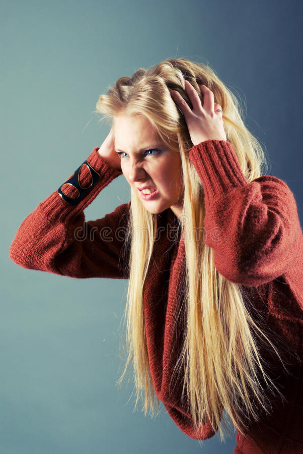 Young blond girl furiously scratches. Her tangled hair on gray background stock image