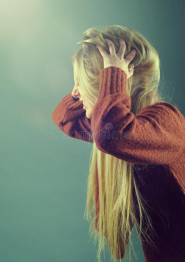Young blond girl furiously scratches her tangled hair. On gray background stock photo