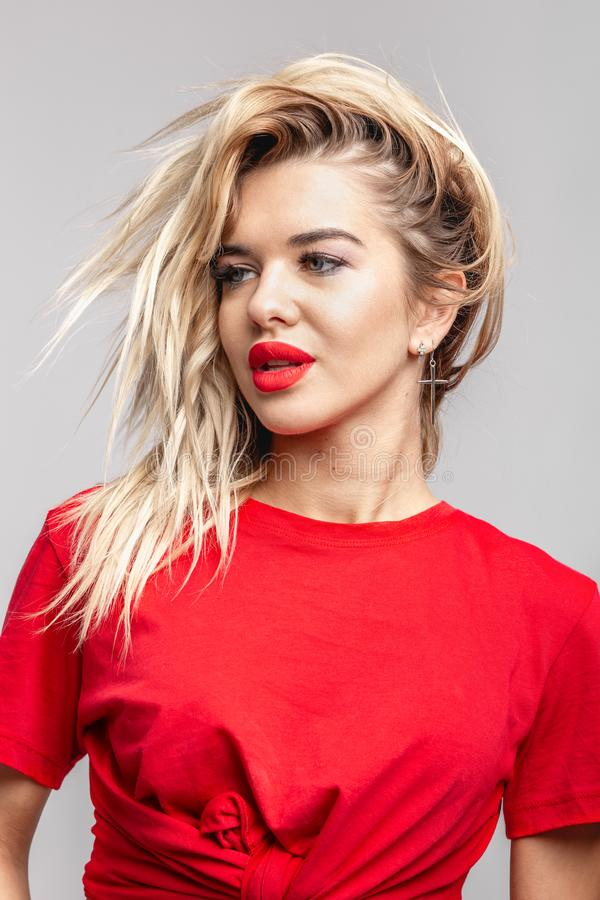 Young blond girl with a red  lipstick short  in a red t-shirt poses staying against a wall in the studio stock photography