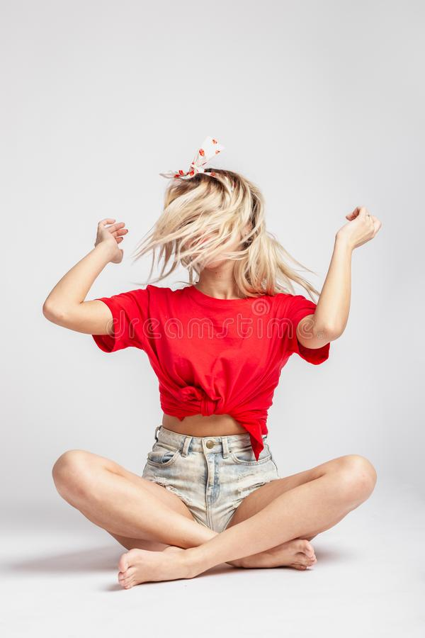 Young blond girl with a ribbon on her head dressed in short denim shorts and a red t-shirt poses sitting on the floor stock photos