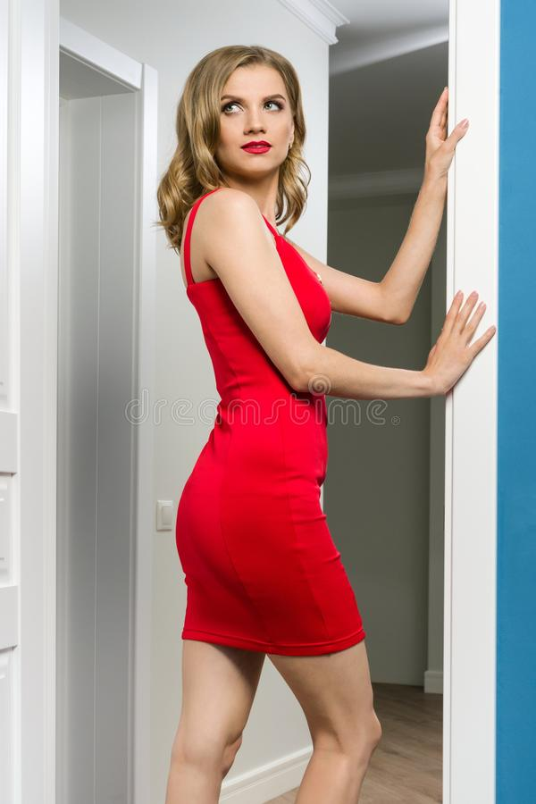 Young blond girl in red dress near white door in the interior of the apartment. Back view royalty free stock photo