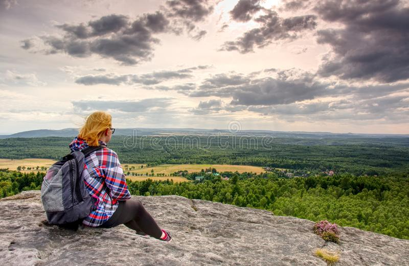 A young blond girl sit on peak and enjoy sun. Woman hiker stock photo
