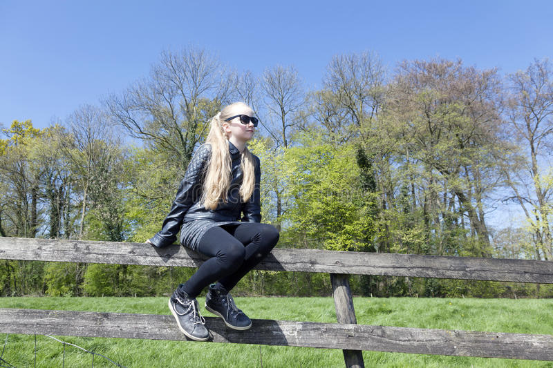 Young blond girl with sunglasses on fence befrore fresh green sp royalty free stock images