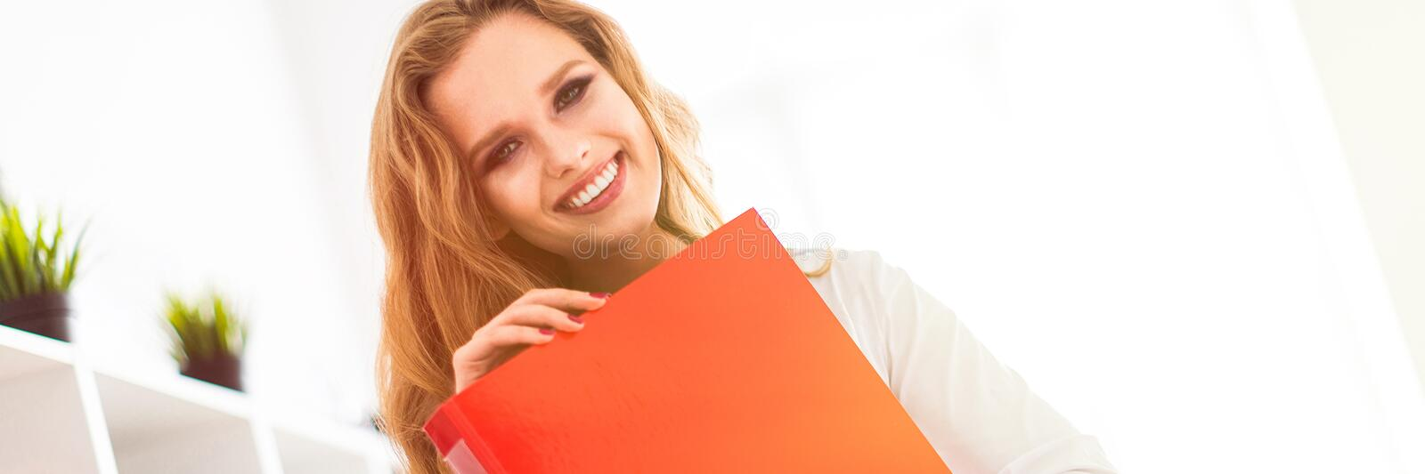 A beautiful young girl stands near a rack in the office and holds a folder with documents. stock images