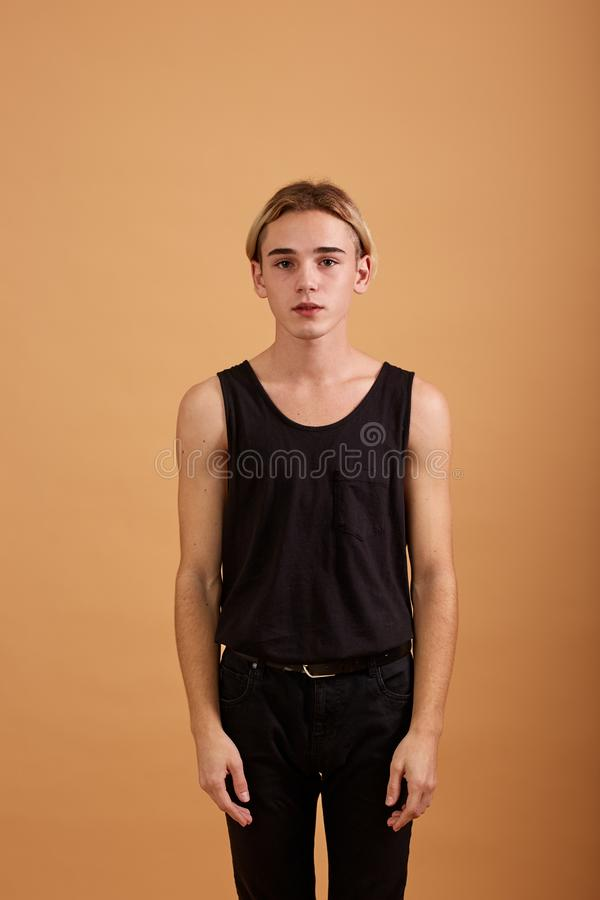 Young blond guy dressed in a black t-shirt and pants posing in the studio on the beige background stock images